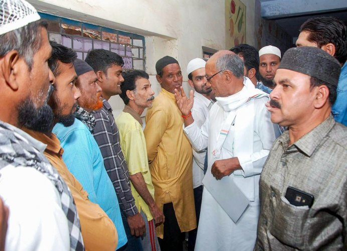 Congress candidate for Bhopal seat Digvijaya Singh interacts with voters at a polling booth during the sixth phase of Lok Sabha polls, in Bhopal. (PTI Photo)
