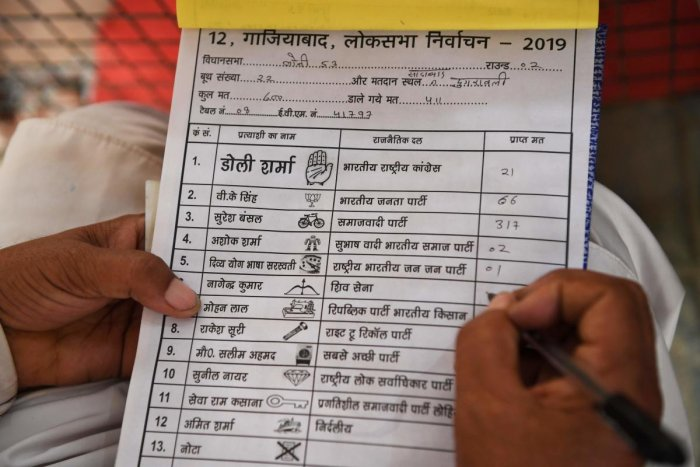 An Indian poll agent notes down details of votes that candidates got after the first round of counting at a counting centre in Ghaziabad. (Photo AFP)