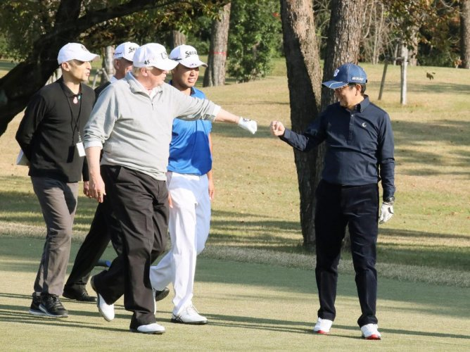 TOPSHOT - In this handout picture released by Japan's Cabinet Public Relations Office via Jiji Press, US President Donald Trump (C) gestures to Japanese Prime Minister Shinzo Abe (R) while playing golf with Japanese professional golfer Hideki Matsuyama (2