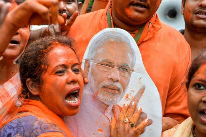 An Indian supporter of Bharatiya Janata Party (BJP) shouts slogans and a cut-out of Indian Prime Minister Narendra Modi as she celebrates on the vote results day for India's general election in Siliguri on May 23, 2019. - Indian Prime Minister Narendra Mo