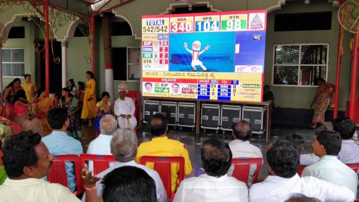 Relatives and friends watch the live telecast of Prime Minister Narendra Modi's victory on a huge LED screen along with a newlywed couple Sangamesh and Thanu in Hubballi on Thursday. DH Photo