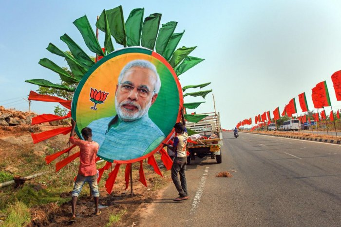 Kanyakumari: Workers place a huge portrait of Prime Minister Narendra Modi along a road ahead of his rally, in Kanyakumari, Thursday, Feb. 28, 2019. (PTI Photo)