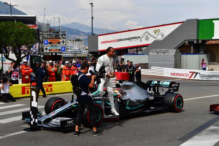 Lewis Hamilton (C) celebrates winning the pole position after the qualifying session