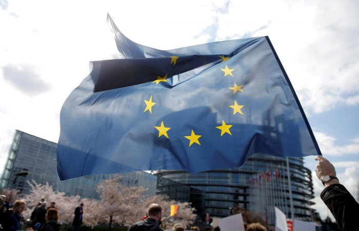 FILE PHOTO: A demonstrator holds an European flag as he takes part in a protest in front of the European Parliament as Members of the European Parliament debate on modifications to EU copyright reforms in Strasbourg, France, March 26, 2019. REUTERS/Vincen