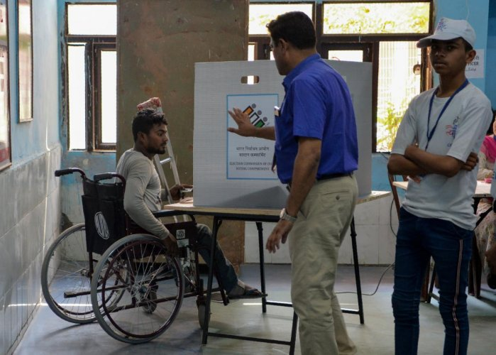 An Indian disabled man casts his vote at a polling station after the Election Commission of India ordered re-polling in Chandni Chowk in the old quarters of New Delhi on May 19, 2019. - (Photo by Sajjad HUSSAIN / AFP)