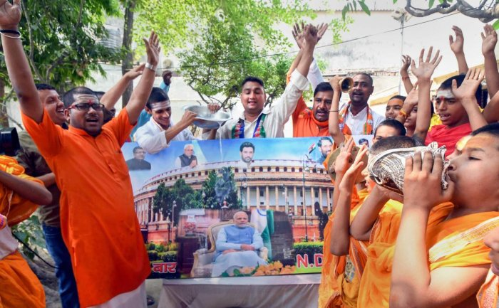 NDA supporters pour milk over a photo of Prime Minister Narendra Modi after their victory at Lok Sabha polls, in Patna, Friday, May 24, 2019. (PTI Photo)