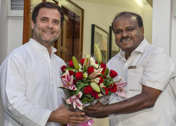 JD(S) leader and Karnataka chief minister-designate H D Kumaraswamy presents a bouquet to Congress President Rahul Gandhi. (Photo PTI)