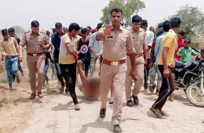 An injured man lynched being the locals over the suspicion of cow slaughter, is being dragged by locals in the presence of police personnel, in Hapur on Monday, June 18, 2018. Kasim (45) was lynched following a minor tiff with a man on a motorcycle in Bacheda village in Pilkhuwa area. (@ Twitter Photo via PTI)