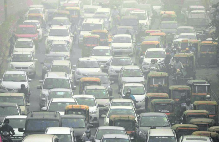 Blanket of threat: Vehicles drive through heavy smog in Delhi. REUTERS