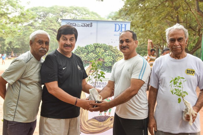Veteran Sandalwood actor Srinath distributed seedlings to the public at Basavanagudi's MN Krishna Rao Park. He also planted a seedling at the park. (DH Photo)
