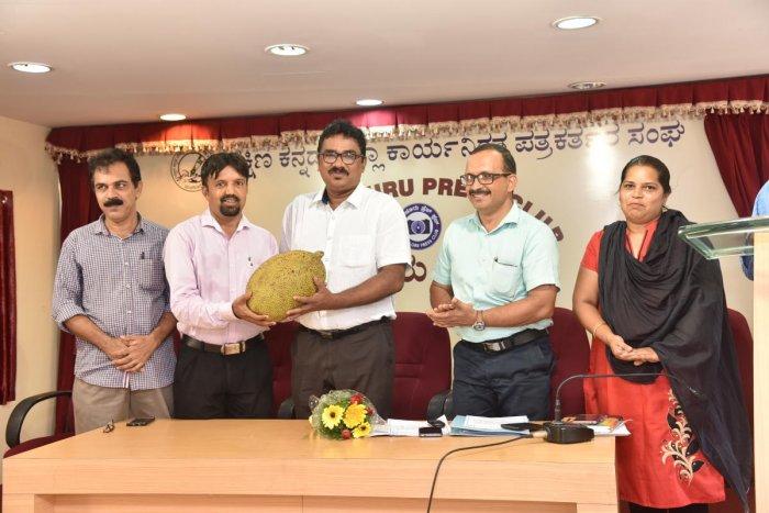 Srinivas Nayak, Dakshina Kannada Working Journalists' Association president, hands over a jackfruit to H R Nayak, Horticulture Department deputy director, during the 'Meet the Press' programme organised at Press Club in Mangaluru.