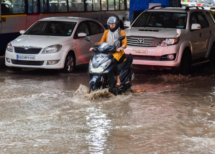 Commuters navigate a waterlogged Okalipuram Road on Wednesday. (DH PHOTO/M S MANJUNATH)