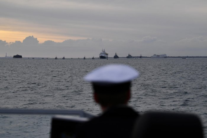 A sailor on board Example, a Royal Navy P2000 watches as the MV Boudicca, carrying veterans, leaves the harbour on its way to Normandy to commemorate the 75th anniversary of D-Day, in Portsmouth, Britain. Reuters