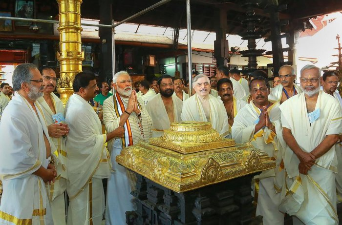 Prime Minister Narendra Modi accompanied by Kerala Governor P. Sathasivam, State Devasom Minister Kadakampally Surendran along with other senior Bharatiya Janata Party (BJP) leaders, offer their prayers at Lord Krishna temple in Guruvayur of Thrissur district. (PTI Photo)