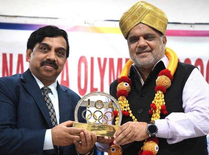 IOA President Narinder Batra (right) presents a memento to Karnataka Olympic Association President K Govindaraj in Bengaluru on Saturday. DH Photo