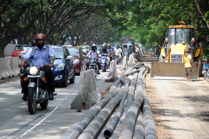 Commuters use a section of the road as white-topping work goes on at CV Raman Road on Saturday. DH Photo/Pushkar V