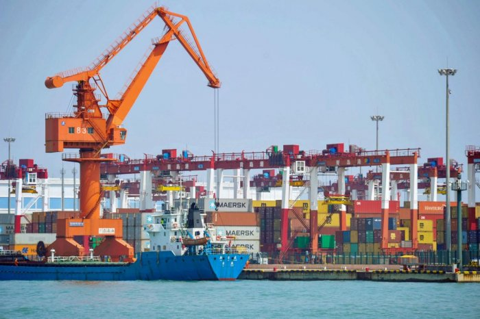 A crane transfers goods at a port in Qingdao, in China's eastern Shandong province on June 10, 2019. (Photo by STR / AFP) / China OUT