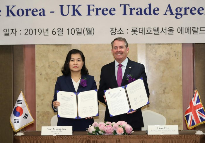 South Korea's Trade Minister Yoo Myung-hee (L) poses with Britain's International Trade Secretary Liam Fox (R) during a signing ceremony of an in-principle South Korea-UK free trade agreement in Seoul. (AFP File Photo)
