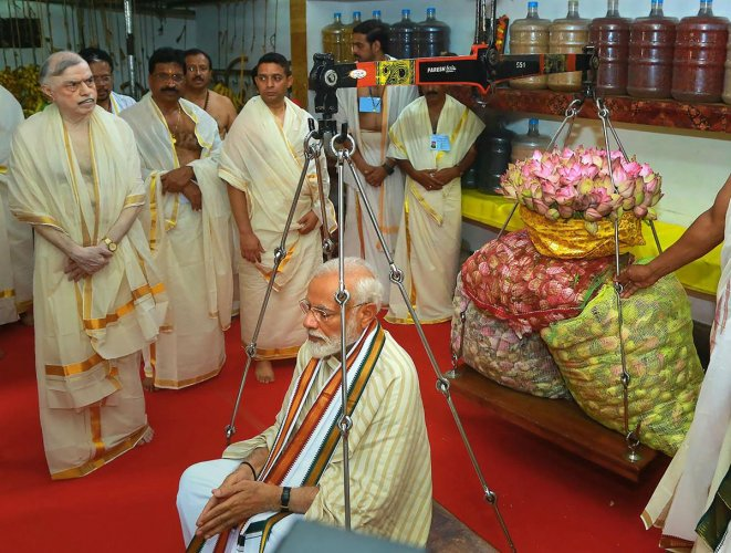 Prime Minister Narendra Modi weighed against lotus flowers as he offers his prayers at Lord Krishna temple in Guruvayur of Thrissur district, Saturday. PTI photo