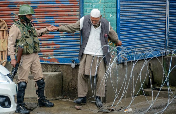 Security person help an elderly man to cross a blocked road during strict curfew imposed to maintain law and order problem following the killing of most wanted militant Zakir Musa, in Srinagar. PTI