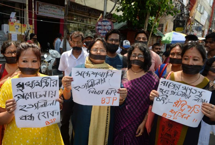 Indian supporters of the Bharatiya Janata Party (BJP) hold placards as they observe 'Black day' during a silent protest rally against the recent killings at Sandeshkhali in West Bengal, in Siliguri on June 10, 2019. (Photo by AFP)