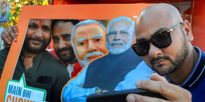 Supporters take selfies with a picture of Prime Minister Narendra Modi as they take part in an event of 'Main Bhi Chowkidar' campaign in Amritsar Monday April 1 2019. | PTI