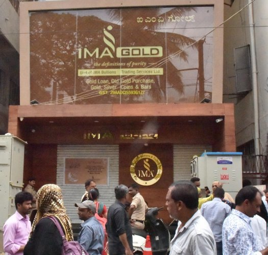 People gather in front of IMA Jewels at Shivajinagar in Bengaluru on Tuesday. DH Photo by Janardhan B K
