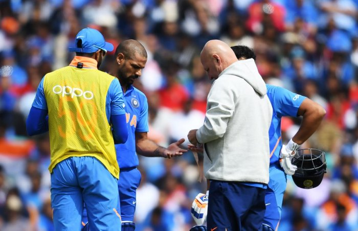 CAUSE FOR WORRY Shikhar Dhawan receives medical treatment after being hit on the hand during India's game against Australia. AFP