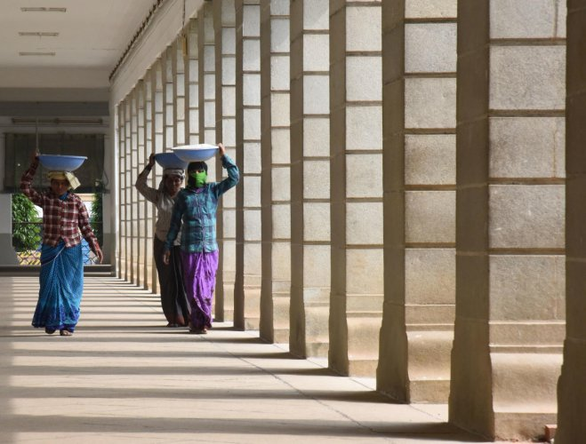 Daily wage labours carry construction materials in Vidhana Soudha, Bengaluru. DH Photo/Janardhan B K