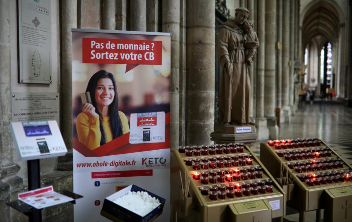 A card machine allowing people to pay without cash for votive candles is seen inside the Cathedral of Notre-Dame in Amiens, France, June 13, 2019. (REUTERS)