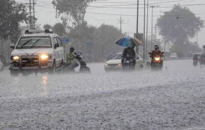 Commuters ride their vehicles during heavy pre-monsoon rains in Bhopal. PTI file photo