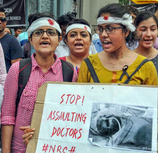 Doctors wear bandages on their heads a sign of protest as they participate in a rally to show solidarity during the strike to protest against an attack on intern junior doctor, at Nil Ratan Sircar Medical College & Hospital, in Kolkata on Saturday. (PTI File Photo)