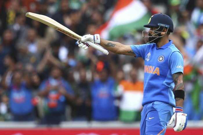 India's captain Virat Kohli raises his bat to celebrates reaching a half-century during the Cricket World Cup match between India and Pakistan at Old Trafford in Manchester, England on Sunday. AP/PTI photo