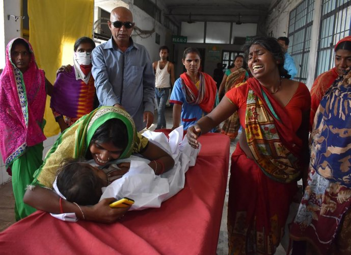 An Indian child arrives in a hospital due to Acute Encephalitis Syndrome (AES) as family members react in Muzaffarpur on June 10, 2019. (Photo by AFP)