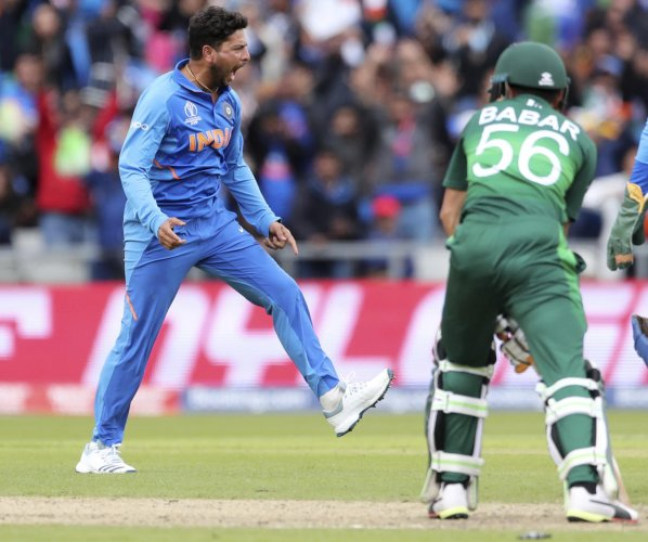 India's Kuldeep Yadav, left, celebrates the dismissal of Pakistan's Babar Azam, right, during the Cricket World Cup match between India and Pakistan at Old Trafford in Manchester, England, Sunday, June 16, 2019. (AP/PTI Photo)