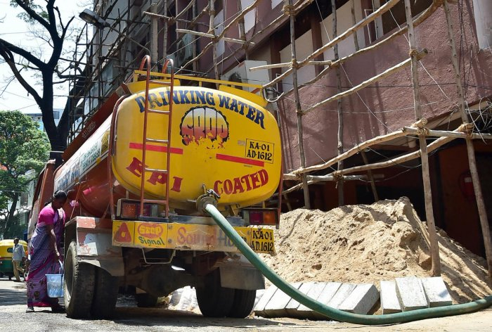 A water tanker supplying water to an apartment complex at Shantalanagar in Bengaluru. DH Photo