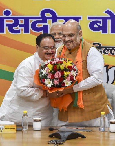 J P Nadda being greeted by BJP chief and Home Minister Amit Shah. PTI