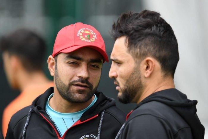 Afghanistan's Rashid Khan talks with Afghanistan's captain Gulbadin Naib. (AFP)