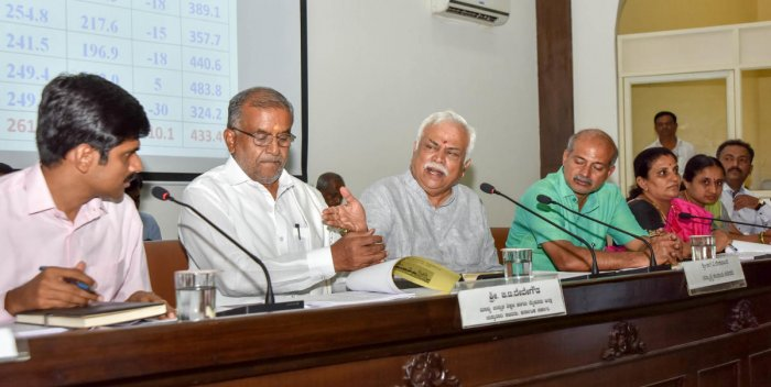 Revenue Minister R V Deshpande addresses officials during a progress review meeting at ZP office in Mysuru on Thursday. Deputy Commissioner Abhiram G Sankar, Higher Education Minister G T Devegowda, Tourism Minister Sa Ra Mahesh and Mayor Pushpalatha Jaga