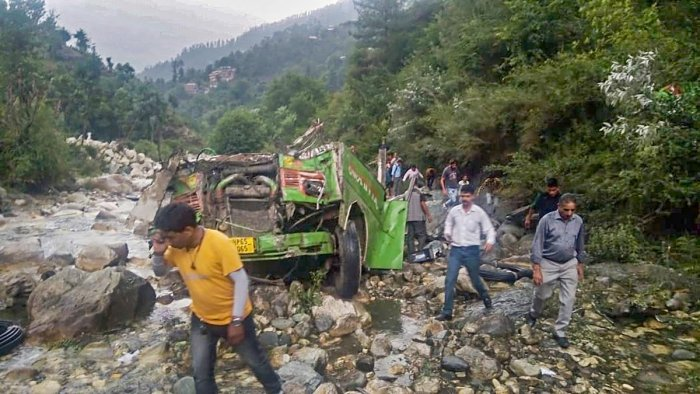 Mangled remains of a private bus after it fell into a 500-ft deep gorge, near Kullu, Thursday. PTI photo