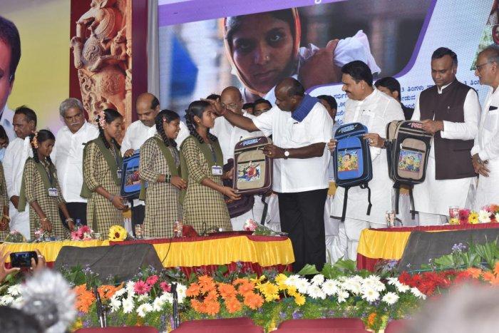 Chief Minister H D Kumaraswamy distributes schools bags to children during Janata Darshan at Chandraki village in Yadgir district on Friday. DH Photo/Prashanth H G