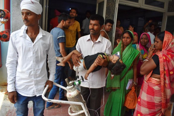 The father (C) of four-year-old kid stands outside Kejriwal hospital along with relatives while holding his son, who is suffering from AES, in Muzaffarpur, Bihar. (AFP)