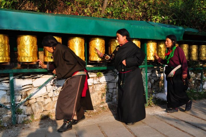 In reverence Tibetan Buddhist women spin the prayer wheel while circumambulating, called 'Ling Khor'.