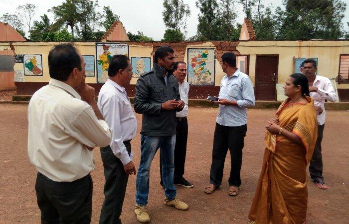 Taluk Panchayat member Appu Ravindra and PWD engineer Channakeshava visit the Government Model Primary School in Closeburn, Kattalekadu, on Monday.