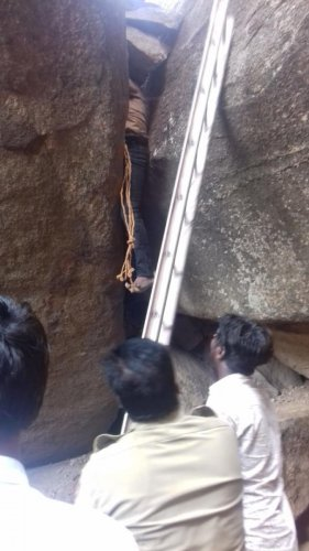 Police and firefighters conduct operations to rescue a man trapped in a narrow opening between the boulders in Hampi on Monday.