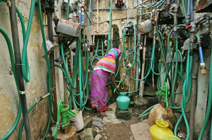 A woman uses a hand pump to fill up a container with drinking water in Chennai. REUTERS