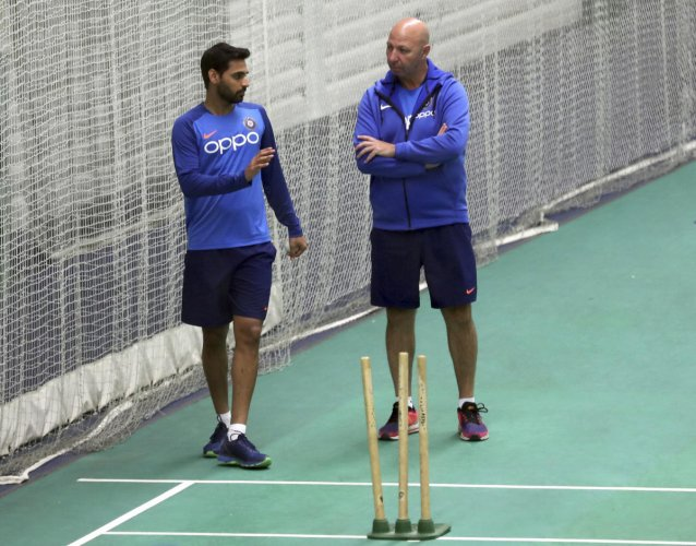 Bhuvneshwar Kumar, left, speaks to team physiotherapist Patrick Farhar during an indoor training session ahead of their Cricket World Cup match against West Indies at Old Trafford. Photo credit: PTI
