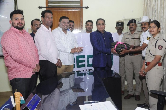 Credai District President Jerry Vincent Dias hands over raincoats to traffic police personnel in Udupi on Friday.