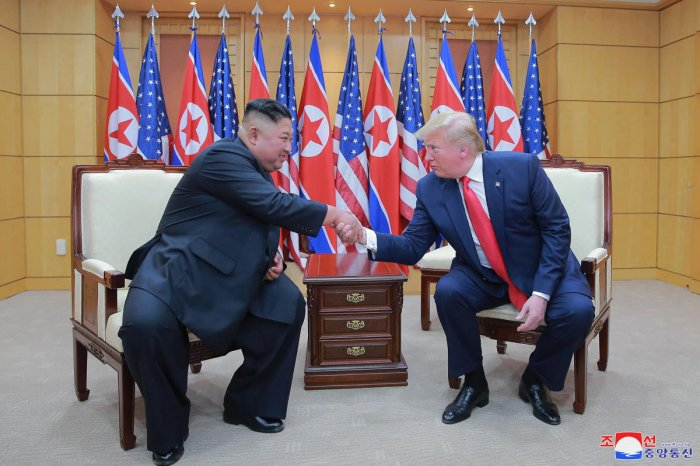 North Korean leader Kim Jong Un, left, and U.S. President Donald Trump shake hands inside the Freedom House on the southern side of Panmunjom, South Korea. (PTI Photo)