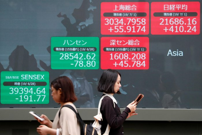 Passersby walk past an electric screen showing Asian markets indices outside a brokerage in Tokyo. (Reuters Photo)